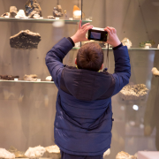 Boy photographing fossils on shelf