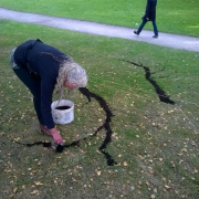 Photo of lady drawing outline of a tree on the ground using soil