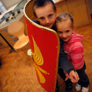 Two children behind a shield at one of the Manchester Museum's Big Saturdays